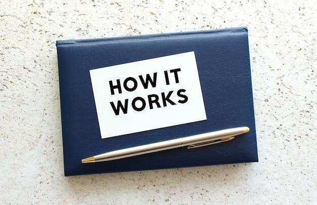 Scrivi come funziona su un biglietto da visita che giace su un taccuino blu accanto alla penna.