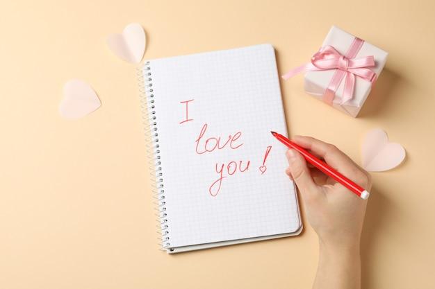 Testo ti amo e mano femminile tiene pennarello su sfondo beige
