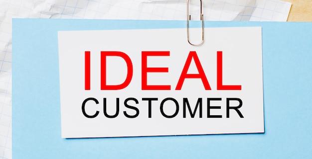 Testo cliente ideale su cartoncino bianco su sfondo blu. concetto di affari