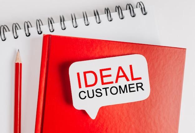 Testo cliente ideale su un adesivo bianco su un blocco note rosso con sfondo di cancelleria per ufficio. piatto disteso sul concetto di business, finanza e sviluppo