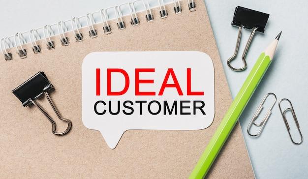 Testo cliente ideale su un adesivo bianco con cancelleria per ufficio