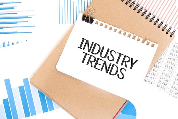 Testo tendenze del settore su foglio di carta bianco e blocco note di carta marrone sul tavolo con diagramma. concetto di affari