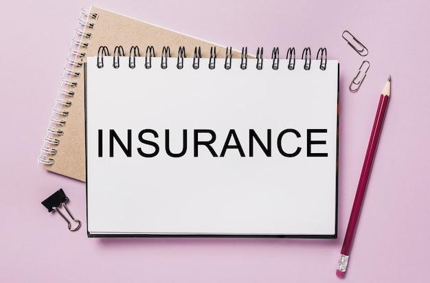 Testo assicurazione su un blocco note bianco con cancelleria per ufficio
