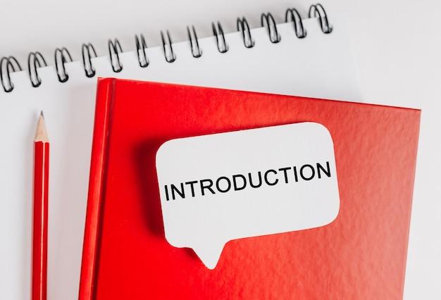 Introduzione al testo un adesivo bianco su un blocco note rosso con sfondo di cancelleria per ufficio. piatto disteso sul concetto di business, finanza e sviluppo