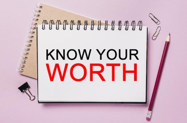 Testo conosci il tuo valore su un blocco note bianco con sfondo di cancelleria per ufficio. piatto disteso sul concetto di business, finanza e sviluppo