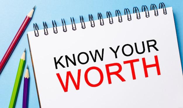 Testo conosci il tuo valore su un blocco note bianco con matite su sfondo blu. concetto di affari
