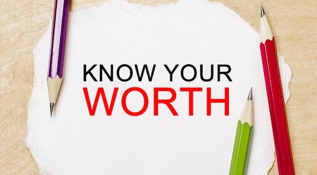 Testo conosci il tuo valore su un blocco note bianco con matite su uno sfondo di legno.