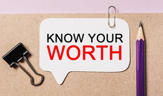 Testo conosci il tuo valore su un adesivo bianco con sfondo di cancelleria per ufficio. piatto disteso sul concetto di business, finanza e sviluppo