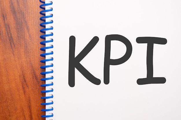 Testo kpi scritto in blocco note, tavolo in legno per ufficio dall'alto, immagine concettuale per titolo blog o immagine intestazione. aspetto di colore vintage invecchiato.