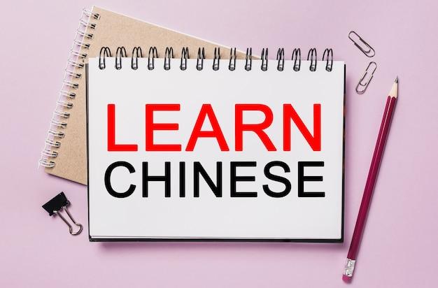 Testo impara il cinese su un adesivo bianco con sfondo di cancelleria per ufficio. piatto disteso sul concetto di business, finanza e sviluppo