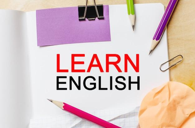 Testo impara l'inglese su uno sfondo bianco con matite, adesivi e graffette. concetto di affari