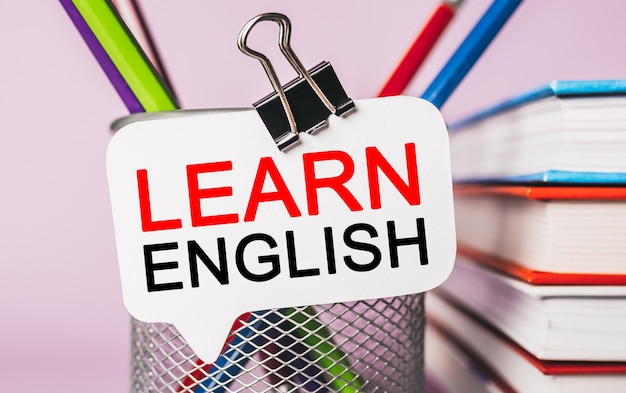 Testo impara l'inglese su un adesivo bianco con sfondo di cancelleria per ufficio. piatto disteso sul concetto di business, finanza e sviluppo
