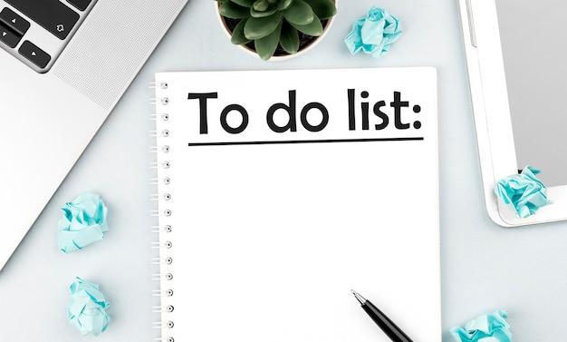 Testo lista da fare sul taccuino. computer portatile, pezzi di carta, penna e pianta sulla scrivania dell'ufficio. disposizione piana, vista dall'alto. concetto di pianificazione.
