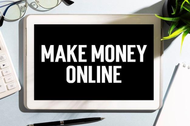Testo make maney online su tablet, calcolatrice, occhiali. concetto di affari. disposizione piatta.