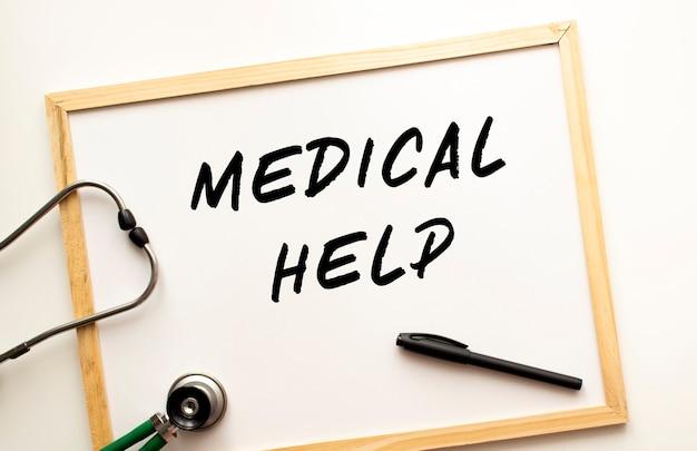 Il testo aiuto medico è scritto su una lavagna bianca con un pennarello. nelle vicinanze c'è uno stetoscopio. concetto medico.