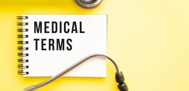 Testo termini medici sul taccuino con lo stetoscopio su priorità bassa gialla.