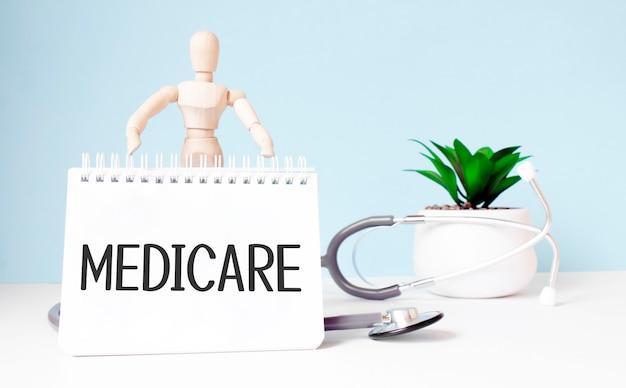 Il testo medicare è scritto su un blocco note e un giocattolo di legno vicino a uno stetoscopio su sfondo blu. concetto medico