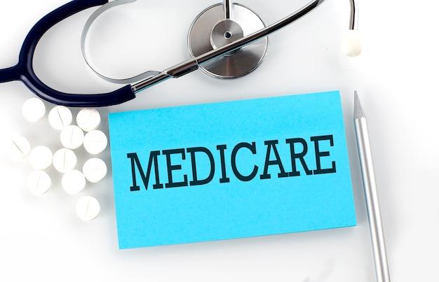 Testo medicare su un tavolo con uno stetoscopio, pillole e penna, concetto medico.