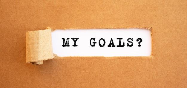 Invia un messaggio ai miei obiettivi dietro carta marrone strappata. per il tuo design, concetto.