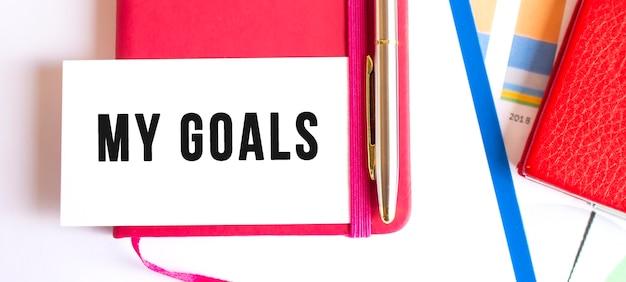 Testo i miei obiettivi su carta bianca che si trova sul blocco note sulla scrivania in ufficio. concetto finanziario.