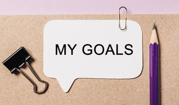 Testo i miei obiettivi su un adesivo bianco con sfondo di cancelleria per ufficio. piatto disteso sul concetto di business, finanza e sviluppo