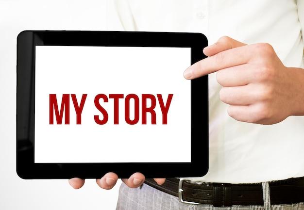 Testo la mia storia sul display del tablet nelle mani di uomo d'affari sul bakcground bianco. concetto di affari