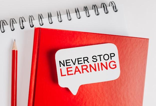 Il testo non smette mai di imparare un adesivo bianco su un blocco note rosso. piatto disteso su affari, concetto di finanza