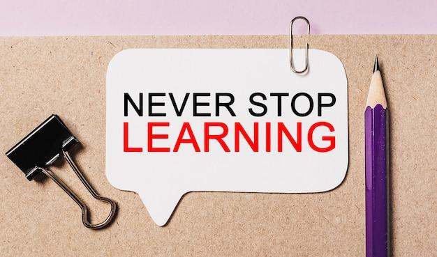 Testo never stop learning su un adesivo bianco con sfondo di cancelleria per ufficio. piatto disteso sul concetto di business, finanza e sviluppo