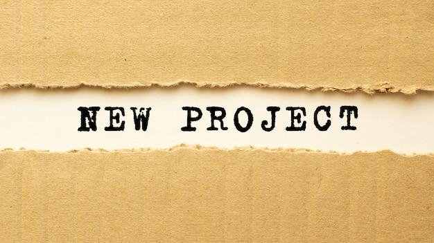 Testo nuovo progetto che appare dietro carta marrone strappata. vista dall'alto.