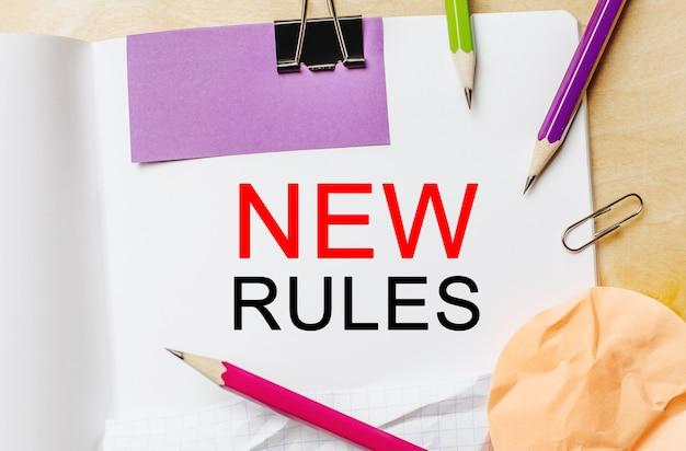Testo nuove regole su uno sfondo bianco nota con matite, adesivi e graffette. concetto di affari
