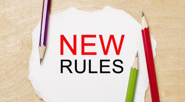 Testo nuove regole su un blocco note bianco con matite su uno sfondo di legno. concetto di affari