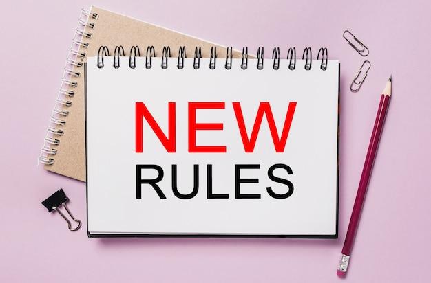 Testo nuove regole su un adesivo bianco con sfondo di cancelleria per ufficio. piatto disteso sul concetto di business, finanza e sviluppo