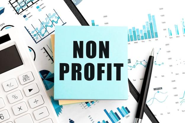 Testo non profit sugli adesivi. penna e calcolatrice negli appunti con grafici, documenti e grafici. concetto di affari. vista dall'alto.