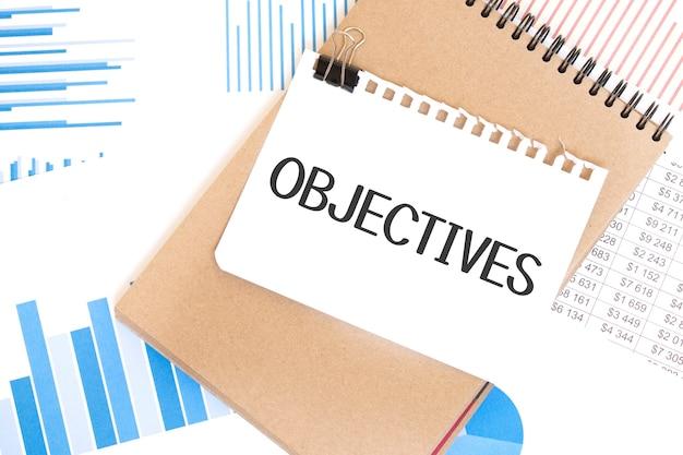 Obiettivi del testo su foglio di carta bianco e blocco note di carta marrone sul tavolo con diagramma. concetto di affari