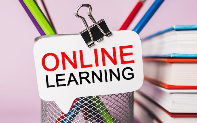 Apprendimento online del testo su un adesivo bianco con sfondo di cancelleria per ufficio. piatto disteso sul concetto di business, finanza e sviluppo