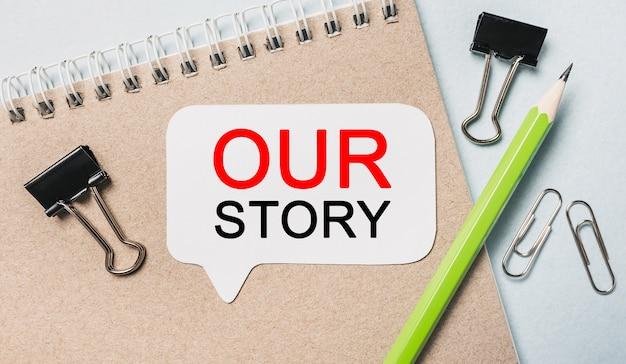 Scrivi la nostra storia su un adesivo bianco con sfondo di cancelleria per ufficio. piatto disteso sul concetto di business, finanza e sviluppo