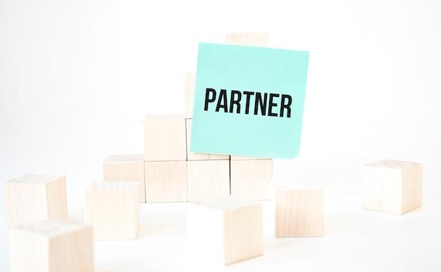 Scrittura del partenariato del testo nella scala del cubo della carta verde. sfondo bianco. concetto di affari