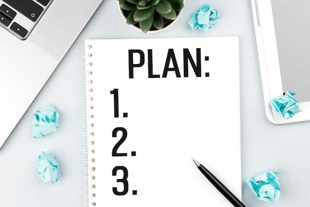 Testo plan sulla nota. computer portatile, pezzi di carta, penna e pianta sulla scrivania dell'ufficio. disposizione piana, vista dall'alto. concetto di pianificazione.