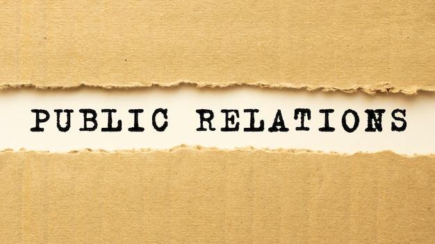 Testo relazioni pubbliche che appare dietro carta marrone strappata