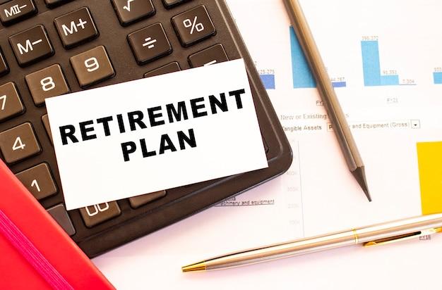 Testo piano di pensionamento su carta bianca con calcolatrice penna in metallo e grafici finanziari