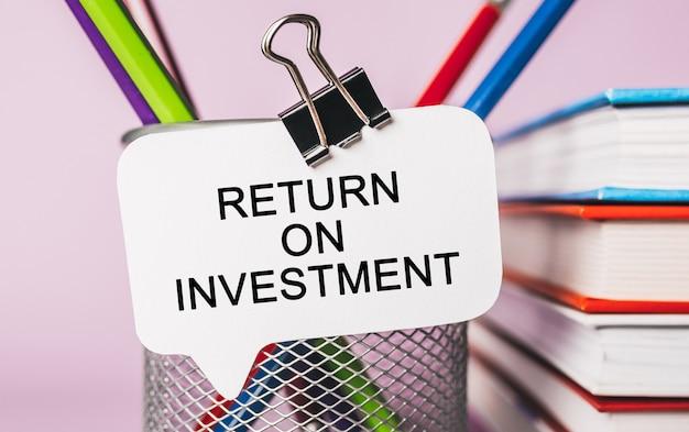 Testo return on investment su un adesivo bianco con sfondo di cancelleria per ufficio. piatto disteso sul concetto di business, finanza e sviluppo