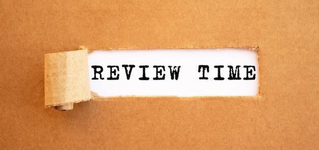 Testo review time che appare dietro carta marrone strappata. per il tuo design, concetto.