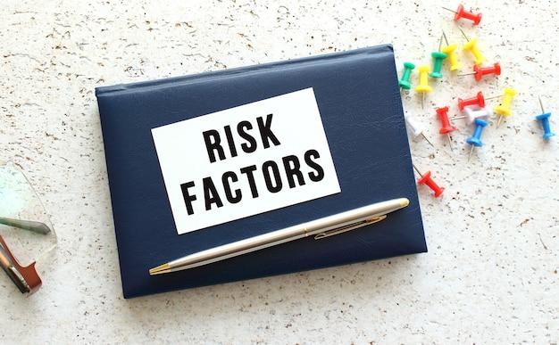 Scrivi fattori di rischio su un biglietto da visita sdraiato su un taccuino blu accanto agli occhiali.