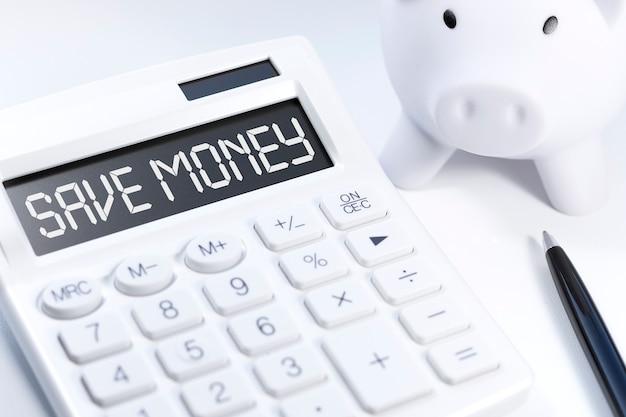 Testo risparmia soldi su calcolatrice, piggy, penna. concetto di affari.