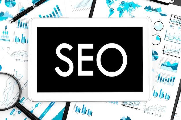 Testo seo search engine optimization su tablet, lente d'ingrandimento, grafico, grafico. concetto di affari. disposizione piatta.