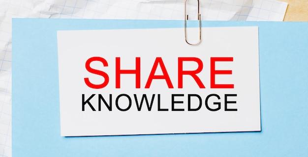 Testo condividi la conoscenza su una carta bianca su uno spazio blu