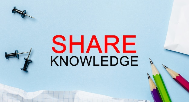 Testo condividi la conoscenza su un blocco note bianco con matite su sfondo blu. concetto di affari
