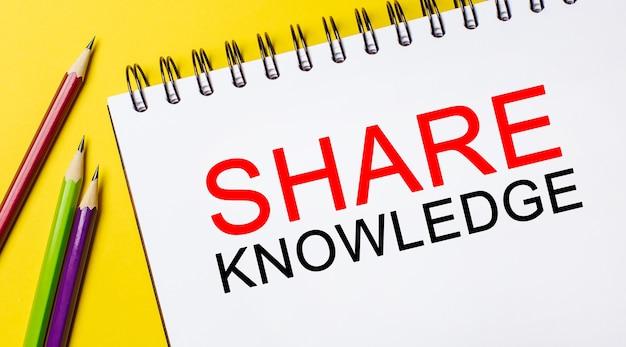 Testo condividi la conoscenza su un blocco note bianco con matite su sfondo giallo.