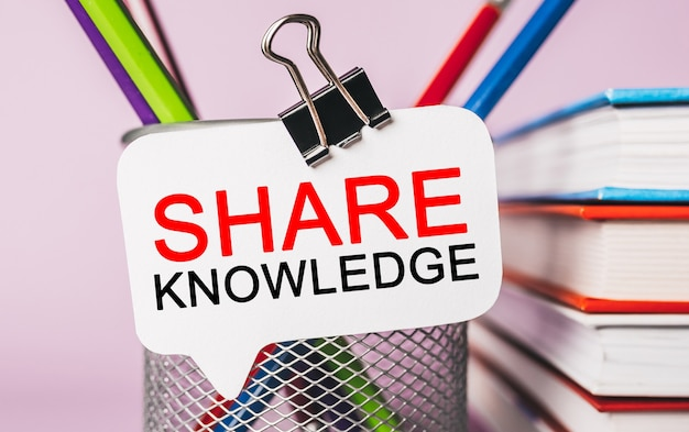 Testo condividi conoscenza su un adesivo bianco con sfondo di cancelleria per ufficio. piatto disteso sul concetto di business, finanza e sviluppo