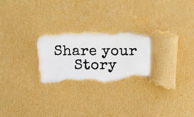 Testo condividi la tua storia che appare dietro carta marrone strappata